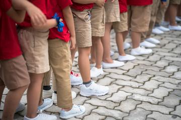 Uniformed children aligned legs