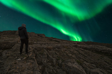 person standing in front of a beautiful northern lights