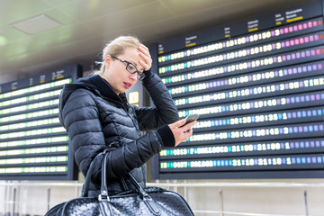 Stressed worried woman in international airport looking at smart phone app information and flight information board, checking her flight detailes.