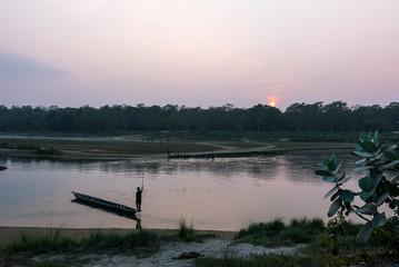 Mann auf einem Boot auf einem Fluss Abendrot