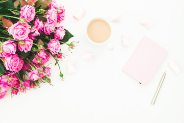 Female desk with bouquet of pink flowers, pink diary, coffee mug and marshmallows on white background. Flat lay. Top view feminine background. Fashion blog.