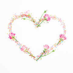 Heart with pink flowers and candy confetti on white background. Flat lay, Top view. Valentine's day composition
