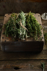 bunches of green herbs on crate