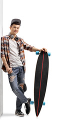 Teenage hipster with a longboard leaning against a wall