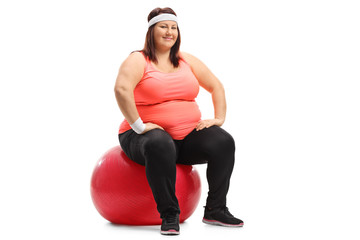 Overweight woman sitting on an exercise ball and looking at the camera