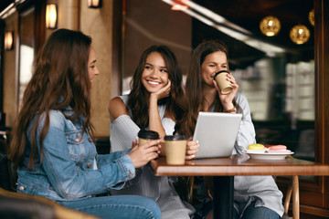 Friends In Cafe. Beautiful Smiling Girls Using Tablet.