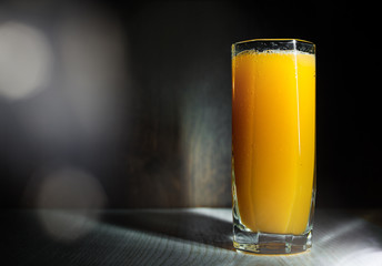 Glass of freshly pressed orange juice on dark black background with copy space