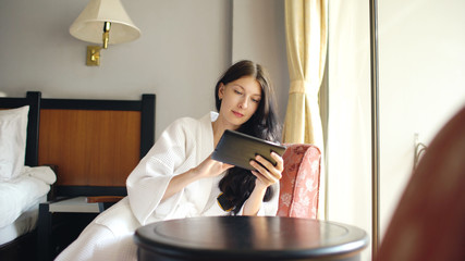 Pretty young woman in bathrobe chatting on tablet computer sitting on chair in hotel room