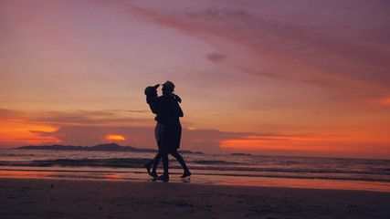 Silhouette of happy loving couple meet and play at the beach on sunset in ocean shore
