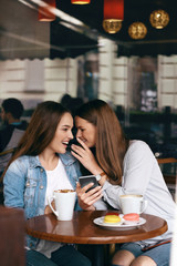 Girls Gossip. Friends With Coffee Speaking In Cafe.