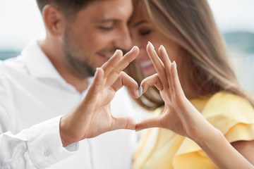 Beautiful Couple In Love Making Heart With Hands.