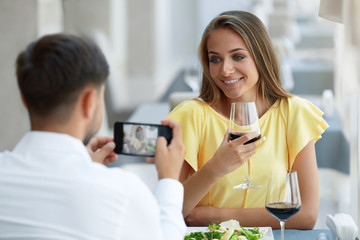 Couple In Restaurant. Man Making Photo Of Woman On Phone