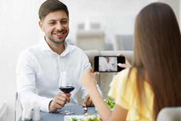 Romantic Dinner. Woman Taking Photos Of Man In Restaurant