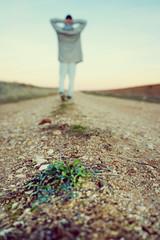 Hombre joven caminando por un camino de tierra al atardecer