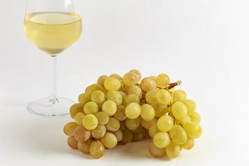 Grappolo di uva bianca con bicchiere di vino