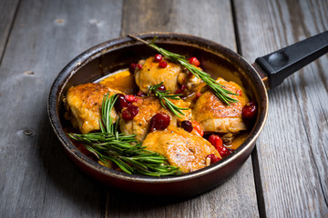 Roasted christmas chicken in a pan with cranberry and rosemary. Selective focus. Shallow depth of field.