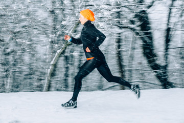 Young woman running outdoors on a cold winter day in snowfall evening time. Motion blurred image