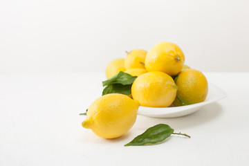 Lemons with leaves and cut lemons on a plate on a white concrete background.