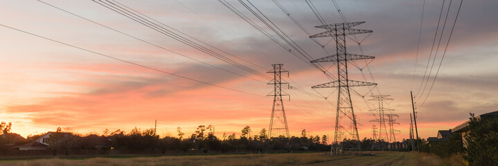 Industrial background group silhouette of transmission tower (or power tower, electricity pylon, steel lattice tower) at bloody red sunset. Texture of high voltage pillar, overhead power line panorama