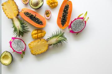 Fresh, exotic, organic fruits on white background. Fruit, papaya, pineapple, dragon fruit, avocado, mango, passion fruit. Asia. Thailand. Not beautiful. Palm leaf