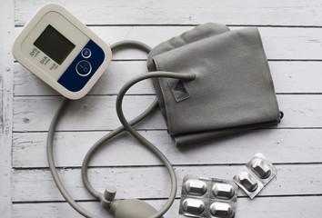 White tonometer on white wooden table for measuring blood pressure.
