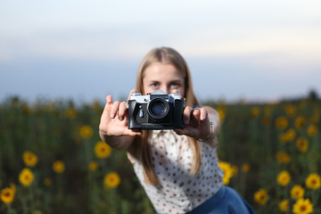 beautiful young girl photographer with photo camera on nature