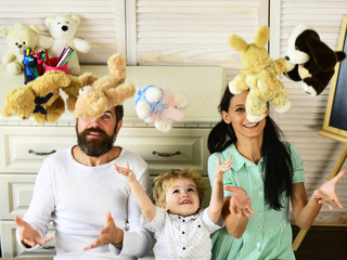 Mom, dad and boy throw toys up on wooden background.