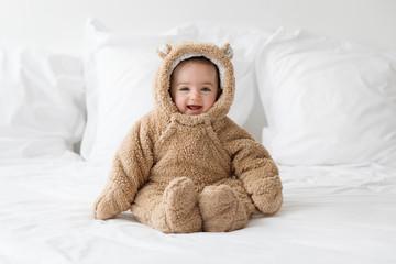 smiling baby wearing bear suit