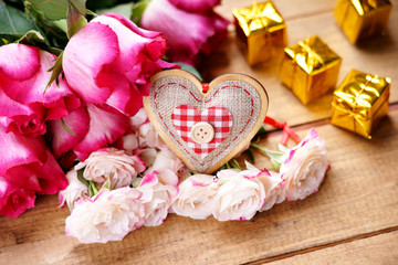 Gift boxes, roses and heart shape on a wooden table