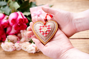 Heart shape in hands, gift boxes, roses on a wooden table