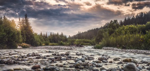 Bela River with Water Flowing over the Rocks at Sunset in Slovakia