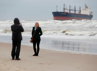 People take a picture in front of the stranded cargo ship Ocean Crown in Klaipeda