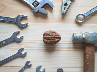 Tool and walnuts on wooden background. The concept of complex problems to be solved.