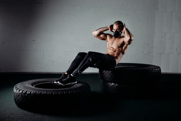Man wearing an elevation mask while doing sit ups on tires