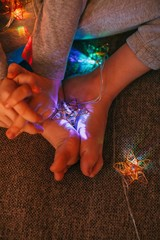 Close-up of a boys hands and feet wrapped in Christmas lights
