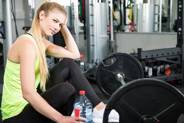 Junge, sexy Frau trainiert im Fitnessstudio ihre Sportübungen mit einer Langhantel, Dehnen, Kurzhantel, macht Pause