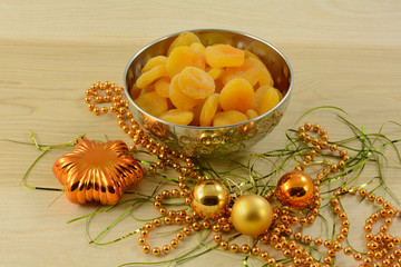 Dried apricots in silver colored bowl with festive Christmas decorations in wooden table
