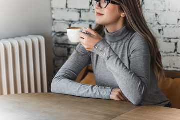 Pretty Caucasian woman sitting at cafe and enjoying coffee.