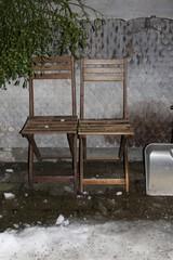 Nachtaufnahme: Holzstühle, Mistelzweige, Schneeschaufel vor aler Schindelwand