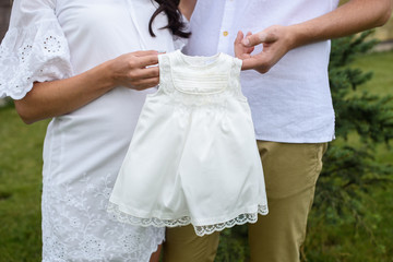 Newborn baby dress in parents hands. Pregnant woman belly.