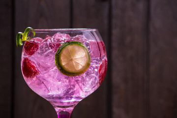 Pink tonic gin with raspberries, wooden background