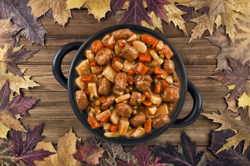 Overhead photo of a pot of beef stew on a wooden table and autumn fall leaves in the background.