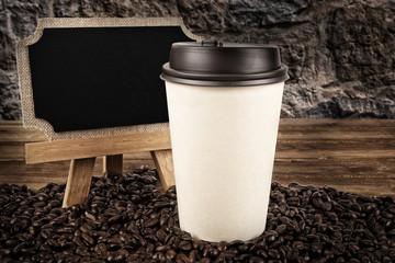 Cup of coffee and coffee beans on old wooden background. Blackboard on the side.
