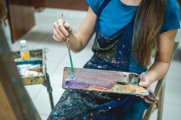 Closeup of female artist hand paint a picture in art studio