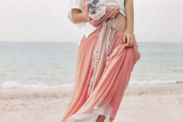 beautiful young stylish woman in pink skirt on the beach close up