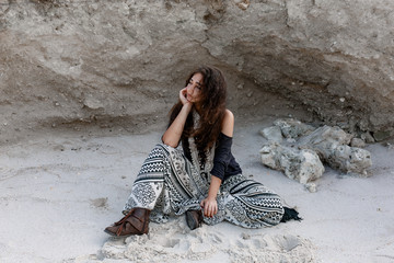 beautiful young boho style girl fashion model sitting on sand on the beach