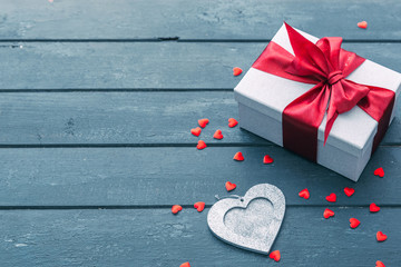 Valentines day hearts and gift box over wooden table background