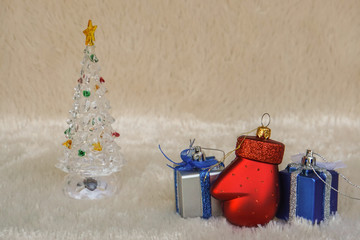 season greeting concept - red glove with Christmas gift with cute Christmas tree