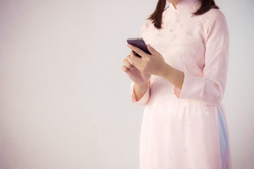 beautiful woman in pink dress and vietnam hat holding smartphone.