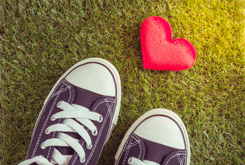 Sport shoes and red heart on grass background